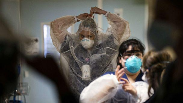 PHOTO: Caregivers put on PPE to enter a COVID-19 patient's room in the ICU of the Sharp Coronado Hospital, amid coronavirus pandemic in Coronado, west of San Diego, Calif., Jan. 20, 2021.  (Etienne Laurent/EPA via Shutterstock)