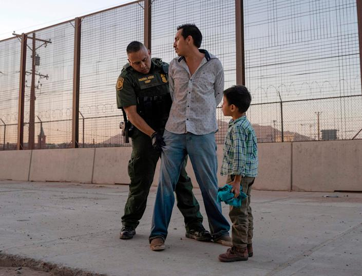 In this file photo taken on May 16, 2019, José, 27, with his son José Daniel, 6, is searched by U.S. Customs and Border Protection Agent Frank Pino in El Paso.