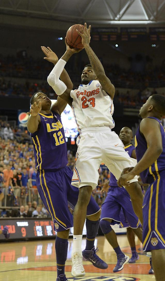 Florida's Chris Walker (23) goes for two points with LSU forward Jarell Martin (12) defending during the first half of an NCAA college basketball game on Saturday, March 1, 2014, in Gainesville, Fla. (AP Photo/Phil Sandlin)
