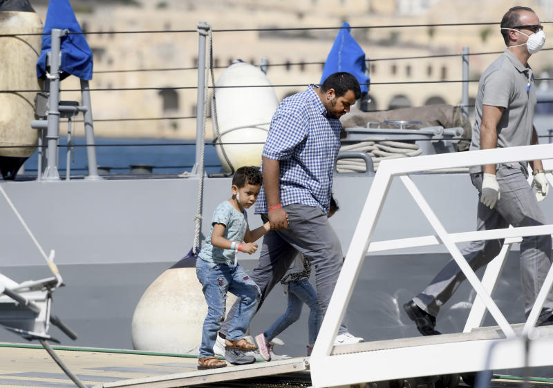A family disembarks from a Maltese naval vessel in the port of La Valletta in Malta after being transferred from a humanitarian ship which rescued them at sea over a week ago, Sunday, Sept. 30, 2018. The Maltese government said Sunday that the migrants would be then transferred in the coming days to the four countries agreeing to accept them: France, Germany, Spain and Portugal. (AP Photo/Jonathan Borg)