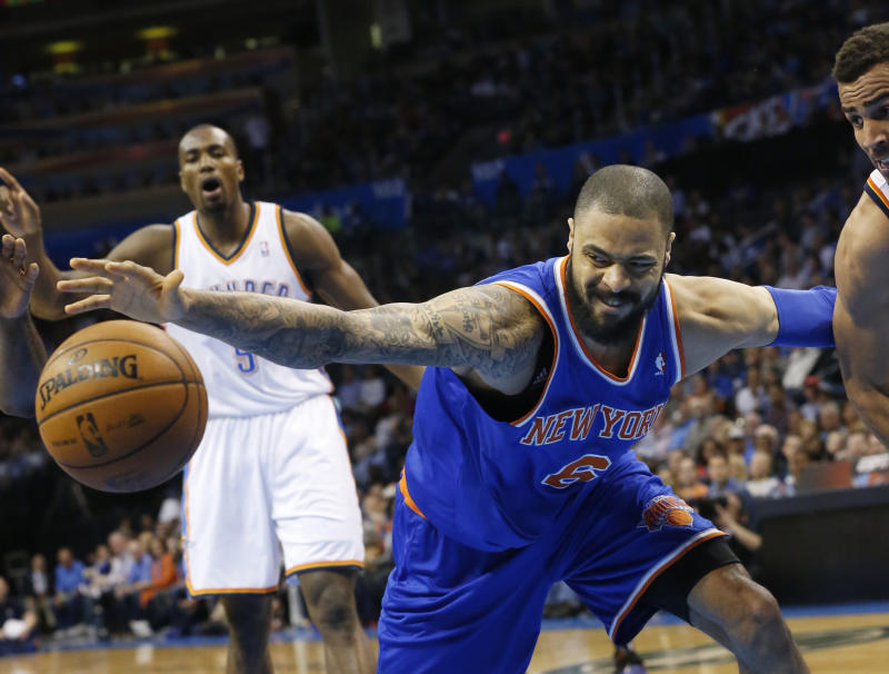 New York Knicks center Tyson Chandler (6) reaches for the ball after it was knocked away by Oklahoma City Thunder guard Thabo Sefolosha, right, in the first quarter of an NBA basketball game in Oklahoma City  Sunday  April 7, 2013.  (AP Photo/Sue Ogrocki)