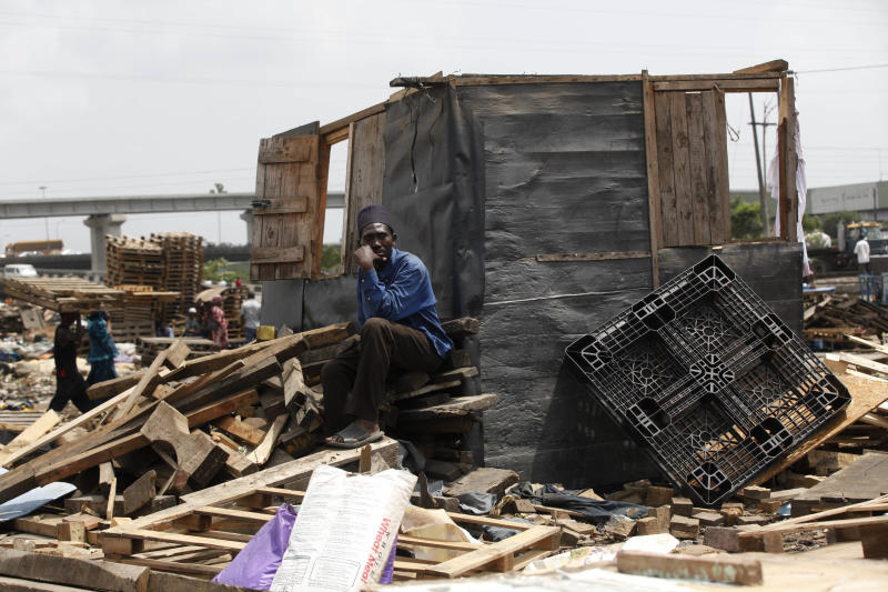 In this image taken Thursday Feb. 28, 2013 a man sits in the rubble of his partly demolished house at Ijora Badia slum in Lagos, Nigeria, The bulldozers arrived at dawn to this neighborhood of shanty homes and concrete buildings in Nigeria's largest city, followed by police officers in riot gear carrying Kalashnikov assault rifles. The police banged on doors, corralling the thousands who live in Ijora-Badia off to the side as the bulldozers' blades tore through scrap-lumber walls, its track grinding the possessions inside into the black murk of swamp beneath it. It left behind only a field of debris that children days later picked through, their small hands dodging exposed rusty nails to pull away anything of value left behind. (AP Photo/Sunday Alamba)