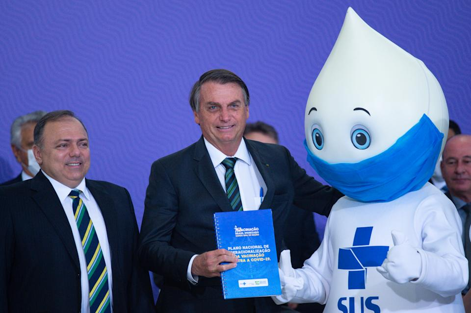 """BRASILIA, BRAZIL -DECEMBER16: Health Minister Eduardo Pazuello (L), Jair BolsonaroPresident of Brazil (C) and """"Zé Gotinha"""" (R), symbol of vaccination in Brazil, duringLaunch of the National Vaccine Operationalization Plan against coronavirus(COVID-19) amidst the coronavirus pandemic at the Planalto Palace on December 16, 2020 in Brasilia.Brazil has over 6.970,000 confirmed positive cases of Coronavirus and has over 182,799 deaths. (Photo by Andressa Anholete/Getty Images)"""