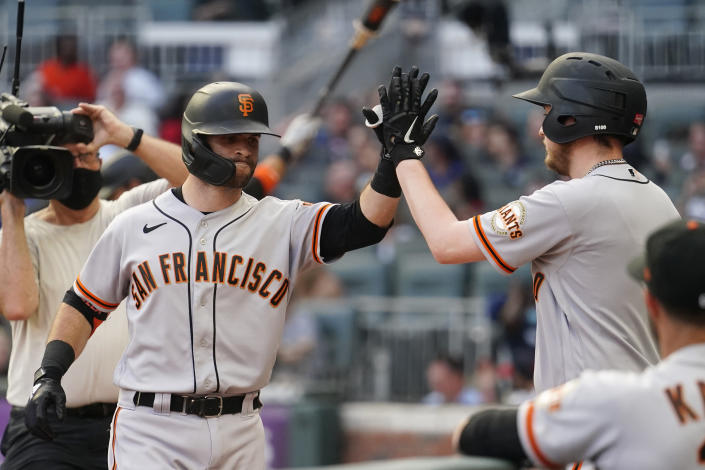 San Francisco Giants' Tommy La Stella, left, is greeted at the dugout after hitting a home run during the first inning of the team's baseball game against the Atlanta Braves on Saturday, Aug. 28, 2021, in Atlanta. (AP Photo/John Bazemore)