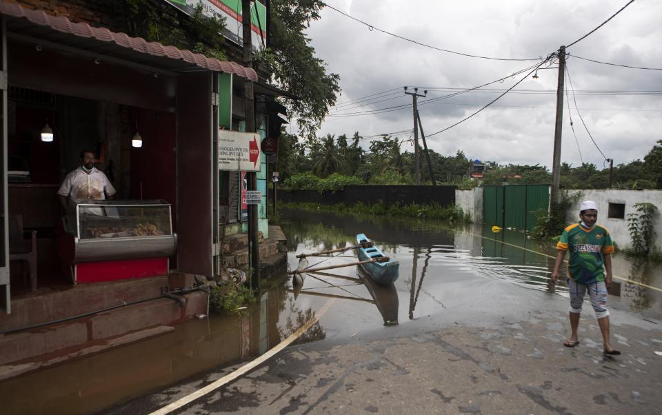 A Sri Lankan vendor waits in his stall as a boat stands in a flooded road at Malwana, on the out skirts of Colombo, Sri Lanka, Saturday, June 5, 2021. Flash floods and mudslides triggered by heavy rains in Sri Lanka have killed at least four people and left seven missing, while more than 5,000 are displaced, officials said Saturday. Rains have been pounding six districts of the Indian Ocean island nation since Thursday night, and many houses, paddy fields and roads have been inundated, blocking traffic. (AP Photo/Eranga Jayawardena)