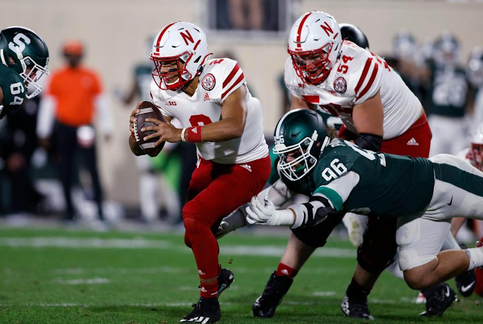 Nebraska quarterback Adrian Martinez escapes from Michigan State's Jacub Panasiuk, right, and Jacob Slade during the second quarter on Saturday, Sept. 25, 2021, in East Lansing.