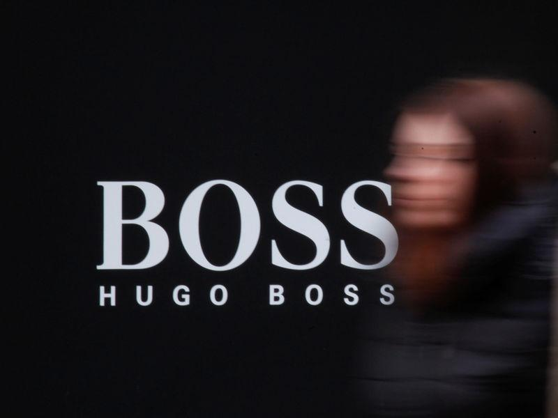 FILE PHOTO: A woman walks past Hugo Boss store logo on a shopping center at the outlet village Belaya Dacha outside Moscow