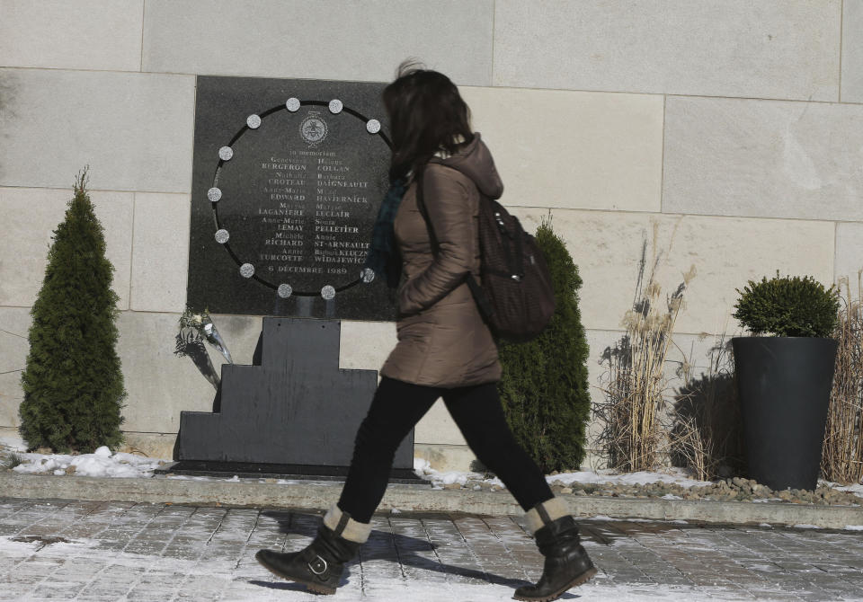 A woman walks past a memorial at University of Montreal's Ecole Polytechnique, the engineering pavilion in Montreal, Quebec December 5, 2014. December 6 marks the 25th anniversary in which 14 women were killed at the polytechnique in a shooting by a lone gunman. REUTERS/Christinne Muschi (CANADA - Tags: CRIME LAW EDUCATION)