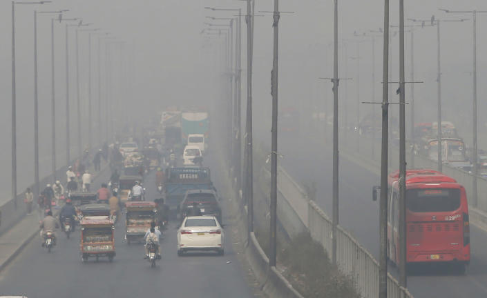FILE - In this Wednesday, Nov. 11, 2020 file photo, vehicles drive on a highway as smog envelops the area of Lahore, Pakistan. The World Health Organization said Wednesday Sept. 22, 2021, the negative health impacts of poor air quality kick in at lower levels than it previously thought, announcing revisions to its guidelines on air quality that set a higher bar for policymakers in a world where 90 percent of people already live in areas with one particularly harmful type of pollutant. (AP Photo/K.M. Chaudary, File)