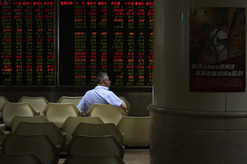 A man sits in front of an electronic board displaying stock prices at a brokerage house in Beijing, Thursday, Aug. 16, 2018. Asian shares are falling as investors fret over slowing economic growth, especially in China. Technology stocks and oil and metals prices skidded overnight on Wall Street.(AP Photo/Andy Wong)