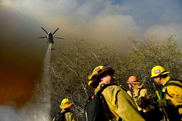 PHOTO: Firefighters keep a lookout as a Los Angeles Fire Department helicopter makes a water drop on the Palisades fire in Topanga State Park in Los Angeles, May 15, 2021. (Patrick T. Fallon/AFP via Getty Images)