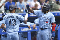 Toronto Blue Jays' Lourdes Gurriel Jr. (13) is congratulated by Vladimir Guerrero Jr. after scoring against the Texas Rangers on a ground out by Marcus Semien during the third inning of the first baseball game of a doubleheader in Buffalo, N.Y., Sunday, July 18, 2021. (AP Photo/Adrian Kraus)