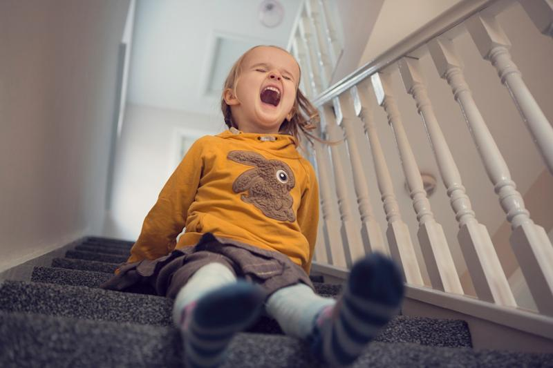 A girl sliding down the stairs.