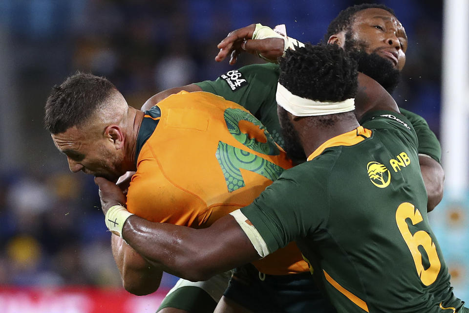 Australia's Quade Cooper, left, is wrapped up by South Africa's Siya Kolisi and Lukhanyo Am, right, during their Rugby Championship match on Sunday, Sept. 12, 2021, Gold Coast, Australia. (AP Photo/Tertius Pickard)