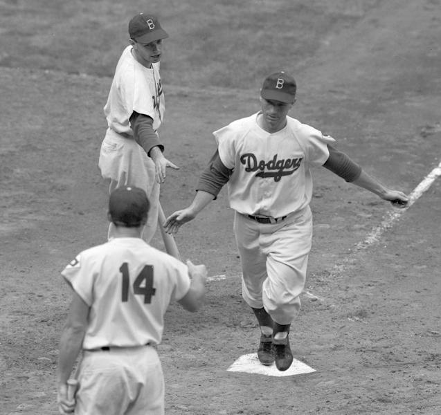 FILE - In this Oct. 1, 1951 file photo, Brooklyn Dodgers' left fielder Andy Pafko is greeted by teammate Gil Hodges (14) and a Dodgers' batboy as he scores on his home run in the second inning of the opening game of the National League playoff series against the New York Giants at Ebbets Field in New York. Pafko, a four-time All-Star who played on the last Chicago Cubs team to reach the World Series, has died at age 92. Pafko died Tuesday, Oct. 8, 2013 of apparent natural causes, according to Kraig Pike, the director of the Pike Funeral Home in Bridgman, Mich. Pafko also played for the Brooklyn Dodgers and the Milwaukee Braves, and played in four World Series during 17 years in the major leagues. (AP Photo/File)