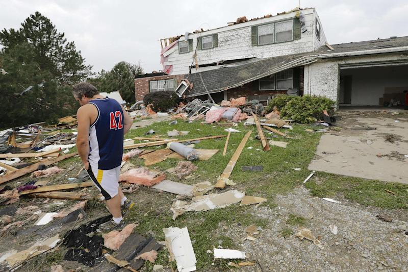 Travis Randall walks through the debris-strewn yard of his parent's home in Hickman, Neb., Friday, Oct. 4, 2013, after it was struck by a tornado. Powerful storms crawled into the Midwest on Friday, dumping heavy snow in South Dakota, spawning a tornado in Nebraska and threatening dangerous thunderstorms from Oklahoma to Wisconsin. (AP Photo/Nati Harnik)