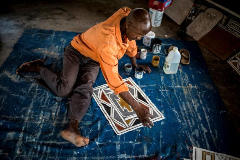 A student of Esther Mahlangu paints a design in the South African artist's home