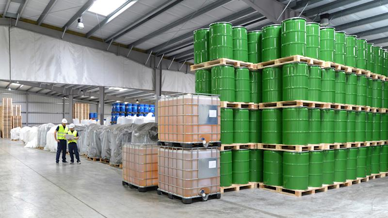 A warehouse filled with green barrels of chemicals.