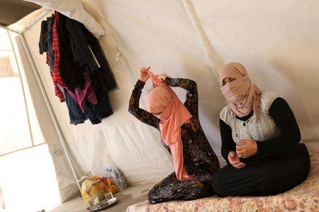 Yazidi sisters, who escaped from captivity by Islamic State (IS) militants, sit in a tent at Sharya refugee camp on the outskirts of Duhok province July 3, 2015. REUTERS/Ari Jala