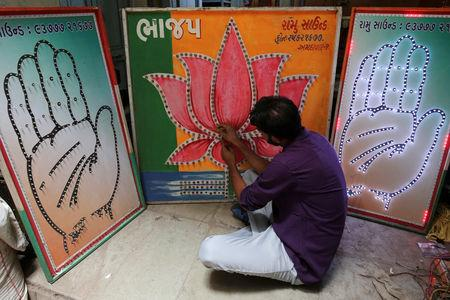 FILE PHOTO: An electrician tests LED-light fitted boards with symbols of India's ruling Bharatiya Janata Party and main opposition Congress party at a workshop in Ahmedabad, India, April 15, 2019. REUTERS/Amit Dave