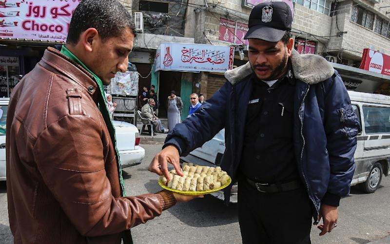 "Hamas called the attack a response to Israeli ""crimes"", and its supporters were later seen distributing sweets in the Gaza Strip to celebrate the attack (AFP Photo/SAID KHATIB)"