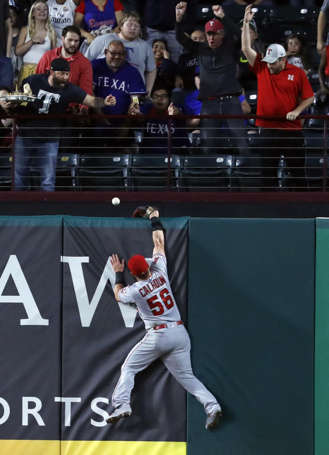 Fans watch as a ball that bounced off the top of Los Angeles Angels right fielder Kole Calhoun's glove falls over the wall for a two-run home run by Texas Rangers' Asdrubal Cabrera during the fourth inning of a baseball game in Arlington, Texas, Tuesday, April 16, 2019. (AP Photo/Tony Gutierrez)