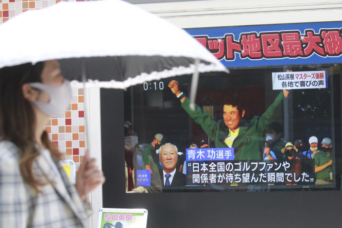 People walk past the tv screen showing the image of Japanese golfer Hideki Matsuyama in a news channel in Tokyo, Monday, April 12, 2021. From Japan's prime minister on down, the country celebrated Matsuyama's victory in the Masters — the first Japanese to win at Augusta National and wear the famous green jacket.(AP Photo/Koji Sasahara)