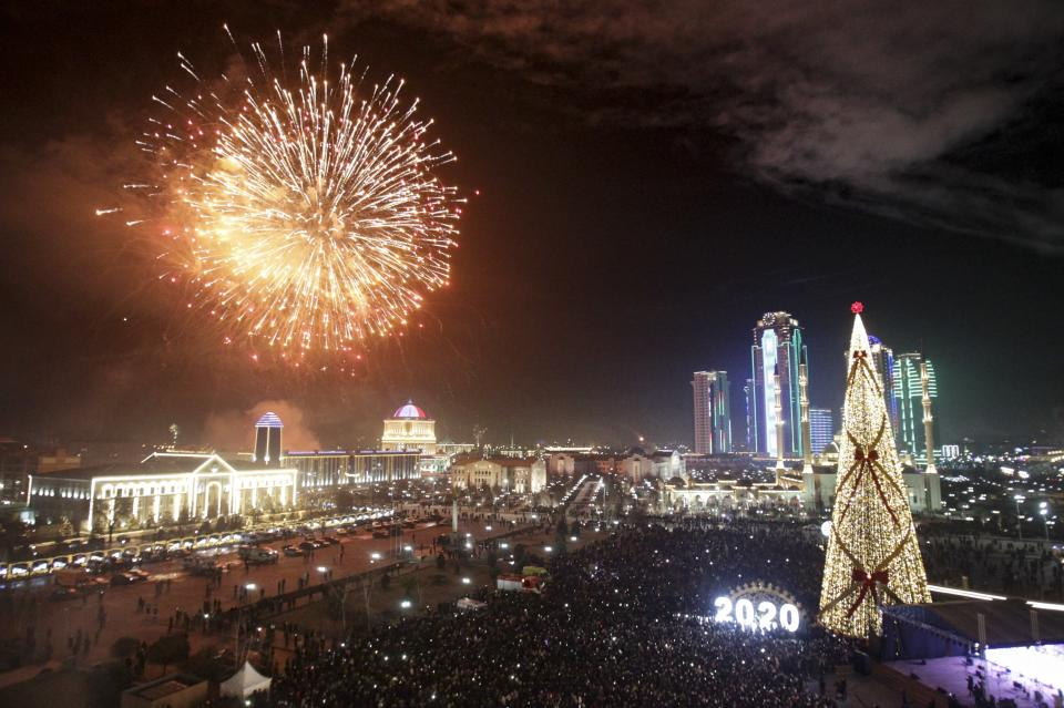 Fireworks explode over a Christmas tree and skyscrapers during New Year's celebrations in Grozny, Russia, Wednesday, Jan. 1, 2020. Russians began the world's longest continuous New Year's Eve with fireworks and a message from President Vladimir Putin urging them to work together in the coming year. (AP Photo/Musa Sadulayev)