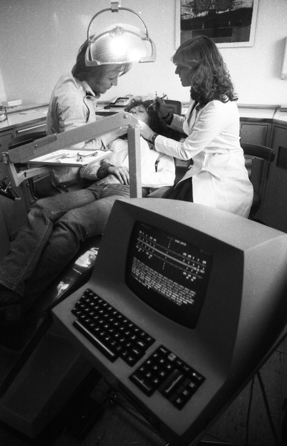 <p>Technology truly began expanding to every facet of the economy and workforce. Here, a dentist and technician use a computer for a patient's checkup in 1979. </p>
