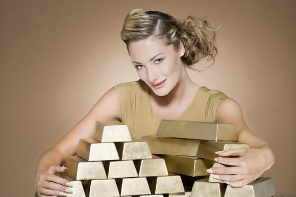 A woman with her arms around stacks of gold bars
