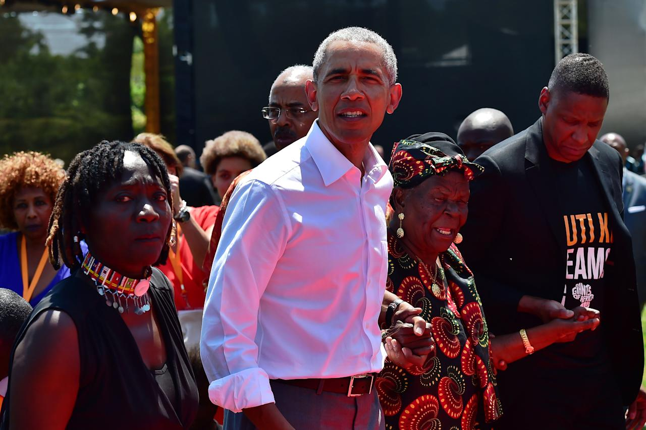 <p>Former US President, Barak Obama (C) with his step-grandmother Sarah (2R) and half-sister, Auma (L) arrive to unveil a plaque on July 16, 2018 during the opening of the Sauti Kuu Resource Centre, founded by his half-sister, Auma Obama at Kogelo in Siaya county, western Kenya. – Obama is in the east african nation for the first time since he left the US presidency and met with President Uhuru Kenyatta and opposition leader Raila Odinga in Nairobi. (Photo: Tony Karumba/AFP/Getty Images) </p>