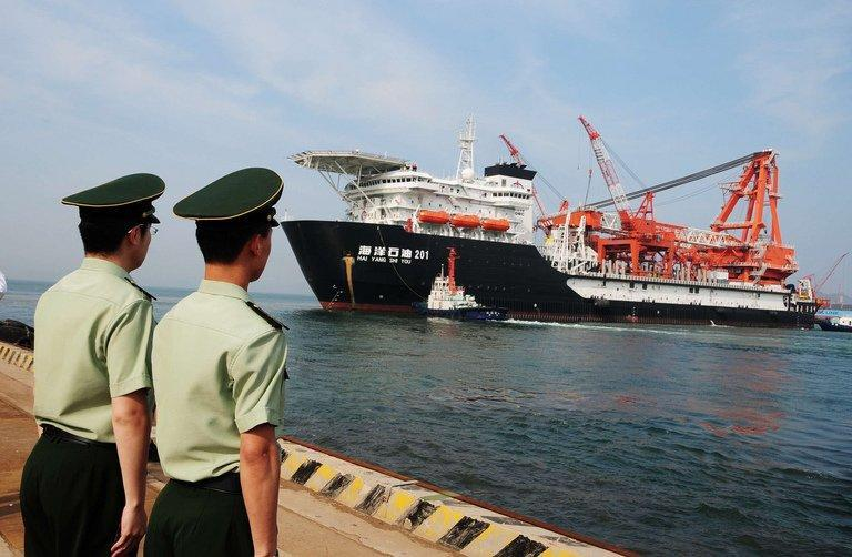 Chinese soldiers watch a China National Offshore Oil Corp. deep-water oil drilling rig leave the of Qingdao, May 21, 2012. China is set to overtake the United States as the world's largest net oil importer from October, according to US figures, due to a combination of rising Chinese demand and increased US production