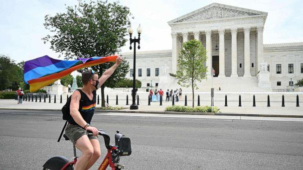 PHOTO: A man waves a rainbow flag as he rides by the US Supreme Court that released a decision that says federal law protects LGBTQ workers from discrimination, June 15, 2020, in Washington,DC. (Jim Watson/AFP via Getty Images)