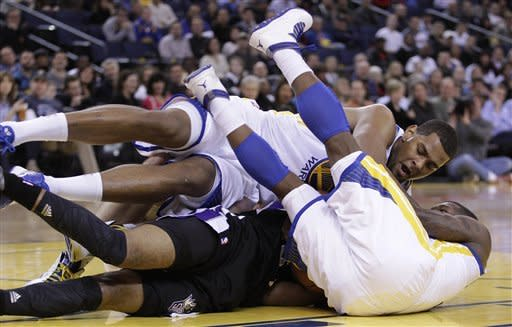 Golden State Warriors' Nate Robinson, right, and Jeremy Tyler, top, fight for the ball with Sacramento Kings' Marcus Thonton during the first half of an NBA basketball game Saturday, March 24, 2012, in Oakland, Calif. (AP Photo/Ben Margot)