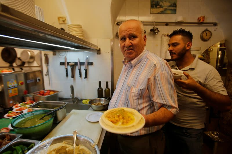Palestinian man George Salameh, 59, owner of Afteem restaurant, carries a plate of Hummus as he works at his restaurant in Bethlehem, in the Israeli-occupied West Bank