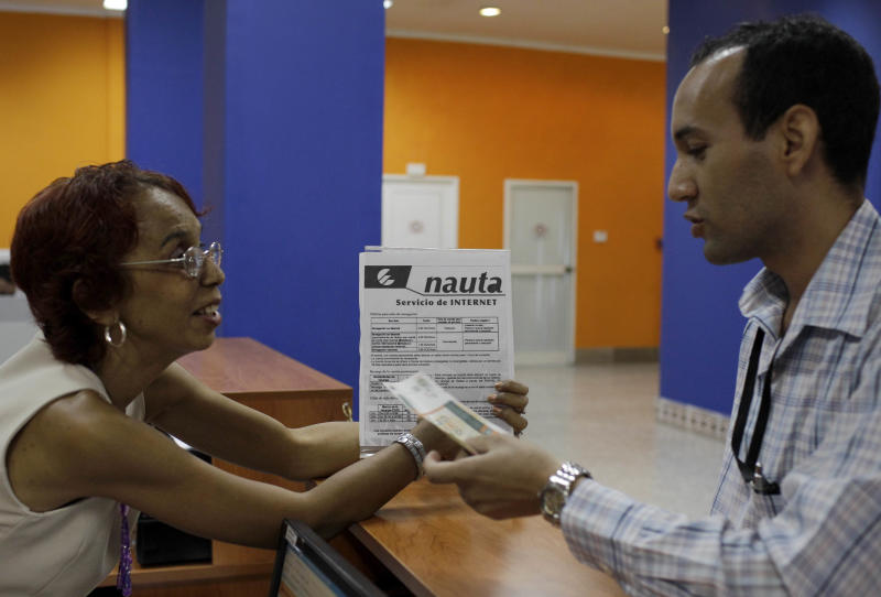 A customer, right, purchases Internet access at a branch office of the state-run telecommunications company, ETECSA, in Havana, Cuba, Tuesday, June 4, 2013. The Cuban government announced it would provide access to the Internet at more than 100 hotspots beginning Tuesday. To date full international access was limited to hotels and in a few special cases, foreign firms. (AP Photo/Franklin Reyes)