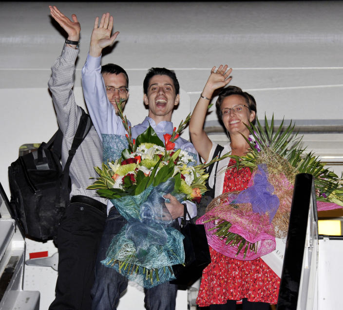 """Freed Americans Shane Bauer, left, Josh Fattal, center, and Sarah Shourd, right, Bauer's fiance, wave from the door to an airplane before leaving for the United States at the airport in Muscat, Oman, Saturday, Sept. 24, 2011. Two Americans freed from an Iranian prison told reporters Saturday they were """"eager to go home"""" just before boarding their flight to the U.S. from Oman, the Gulf state that helped mediate their release after more than two years in custody on accusations of spying. Josh Fattal and Shane Bauer were scheduled to arrive home on Sunday, according to Samantha Topping, a spokeswoman for their families. The two were released from Tehran's Evin prison under a $1 million bail deal and arrived in Oman on Wednesday in the first leg of their journey home. There they were reunited with joyful relatives."""