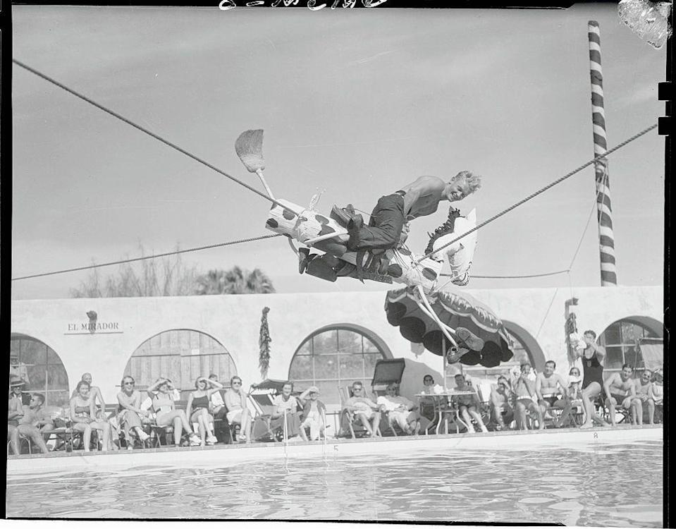<p>The Olympic diver rides a wooden horse suspended above the pool at the El Mirador Hotel. Riley, whose full name is Michael Galitzen, won four medals (including one gold) at the Summer Olympic Games in 1928 and 1932.</p>