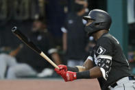 Chicago White Sox's Eloy Jimenez watches his ball after hitting a sacrifice fly in the ninth inning in a baseball game against the Cleveland Indians, Wednesday, July 29, 2020, in Cleveland. Yoan Moncada scored on the play. (AP Photo/Tony Dejak)