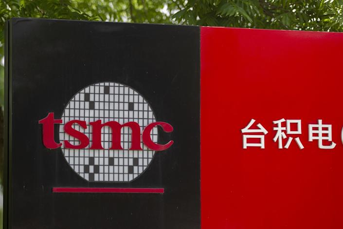 A sign with a company logo with the lowercase letters t-s-m-c next to white Chinese characters on a red background