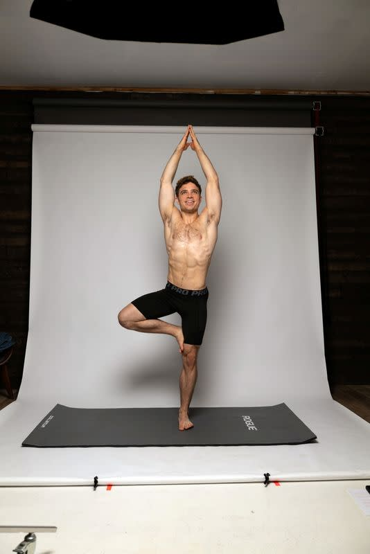 Julian Shaw does a yoga pose in front of a white screen