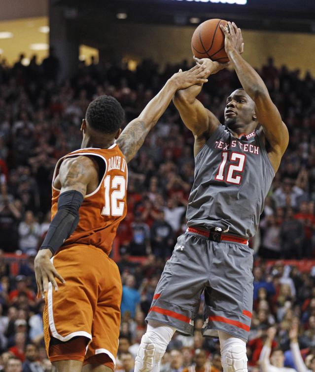"Texas Tech's <a class=""link rapid-noclick-resp"" href=""/ncaab/players/126217/"" data-ylk=""slk:Keenan Evans"">Keenan Evans</a> (12) scores the game-winning basket over Texas' Kerwin Roach (12) during overtime in an NCAA college basketball game Wednesday, Jan. 31, 2018, in Lubbock, Texas. (AP Photo/Brad Tollefson)"