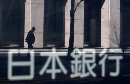 FILE PHOTO: A man walking past a building is reflected in a sign board of the Bank of Japan building in Tokyo January 22, 2014. REUTERS/Yuya Shino/File Photo