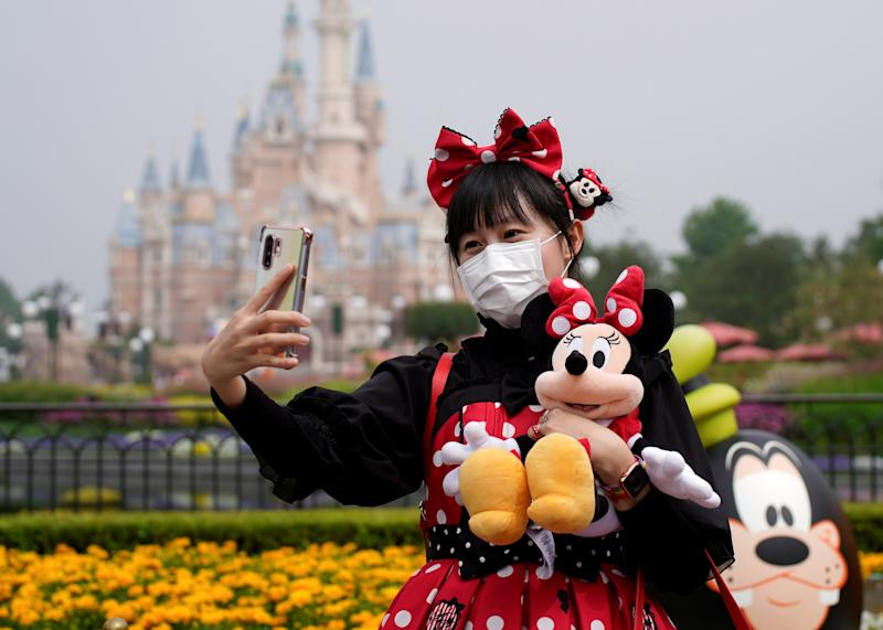 A visitor dressed as a Disney character takes a selfie while wearing a protective face mask at Shanghai Disney Resort as the Shanghai Disneyland theme park reopens following a shutdown due to the coronavirus disease (COVID-19) outbreak, in Shanghai, China May 11, 2020. REUTERS/Aly Song TPX IMAGES OF THE DAY