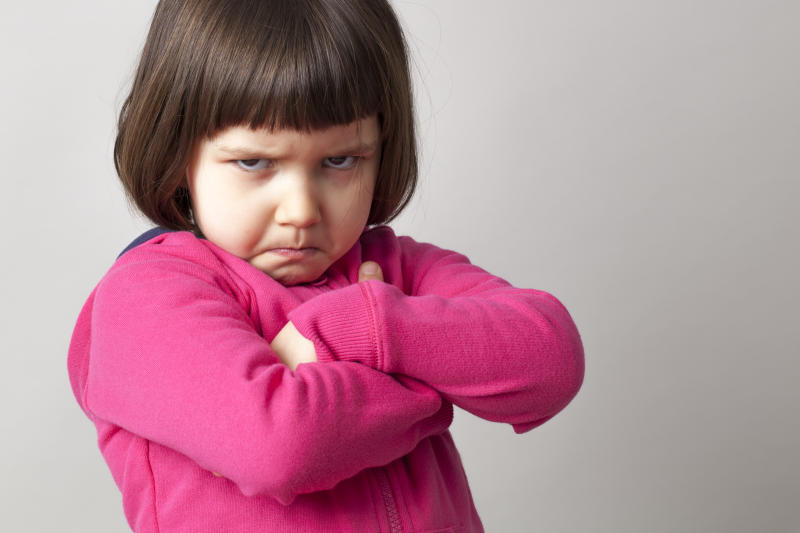 unhappy boyish 4-year old girl expressing disagreement with body language