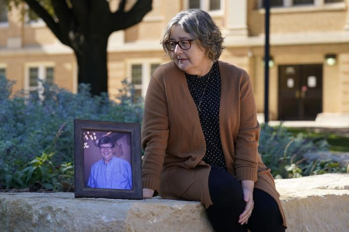 Debbie Riggs poses for a photo, sitting by a portrait of her late husband, Mark Riggs on the campus of Abilene Christian University, Wednesday, Dec. 16, 2020, in Abilene, Texas. Mark, who was a professor at the school, passed away of COVID-19 last Monday. Pressure is intensifying on governors who haven't issued mandates as new coronavirus cases and deaths soar before Christmas. But the debate over mandates and lockdowns often drowns out the reality of whether the restrictions enacted are actually enforced. In the rugged West Texas town of Abilene, the number of deaths has doubled over the past month and intensive care unit beds have been full for weeks. (AP Photo/Tony Gutierrez)