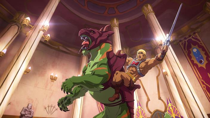 """In a CG animated still from Masters of the Universe: Revelation, He-Man wears a silver chest plate with a red """"H"""" in the center, a golden armored belt and golden wrist plates. He raises his silver sword atop Battle Cat, a green tiger with orange stripes and maroon armor on his hind legs. The two are in the center of a throne room."""