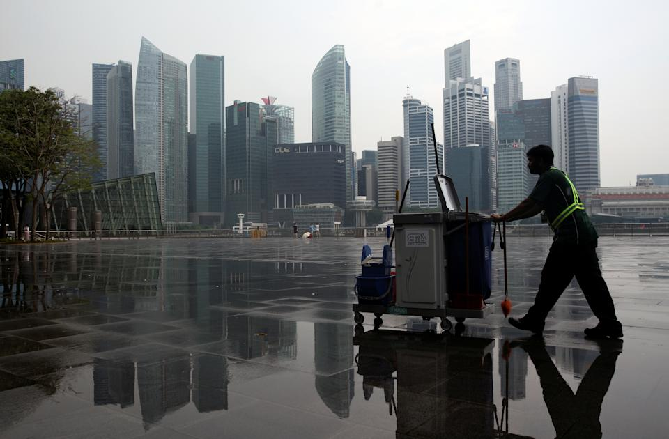 A cleaner passes the city skyline after a morning shower in Singapore April 12, 2016. REUTERS/Edgar Su