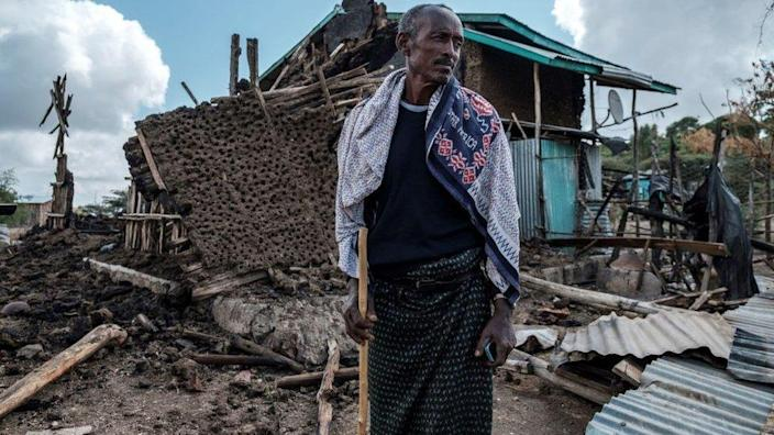 A man stands in front of his destroyed house in the village of Bisober in Ethiopia's Tigray region, on December 9, 2020.