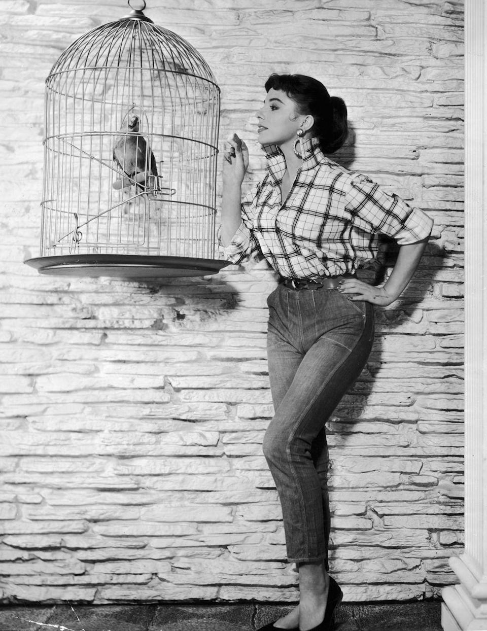 """<p>Actress Joan Collins wore her jeans uncuffed — and significantly more fitted in the leg. She's <a href=""""http://www.stuff.co.nz/life-style/fashion/6572112/I-can-still-rock-jeans-Joan-Collins"""" rel=""""nofollow noopener"""" target=""""_blank"""" data-ylk=""""slk:famously said"""" class=""""link rapid-noclick-resp"""">famously said</a> that she doesn't think women over 40 should wear blue jeans, but here, she's just 22 years old. (Also: we disagree with that statement of hers.)</p>"""